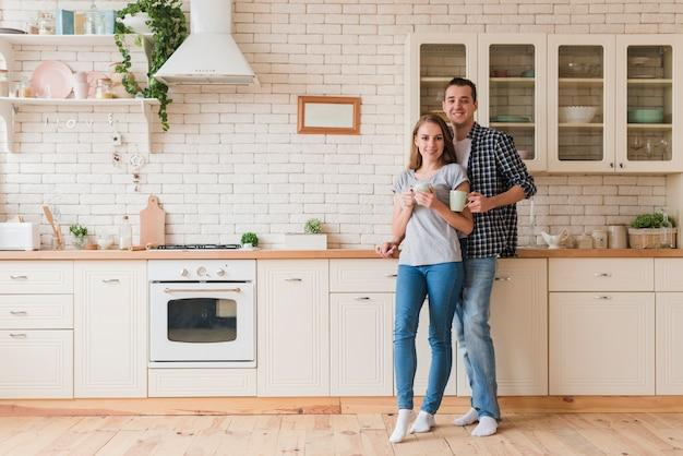 Sonriente pareja descansando en la cocina y saboreando el té