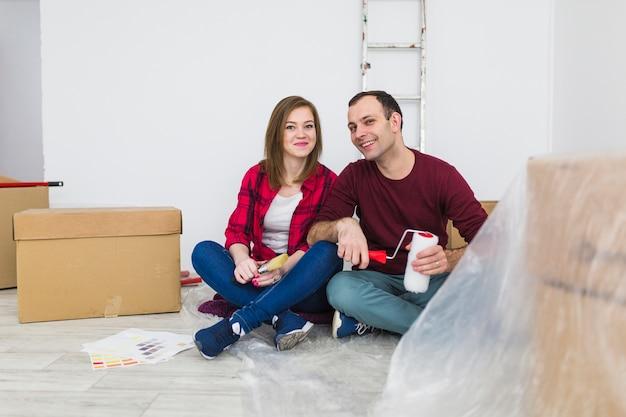 Sonriente pareja descansando en el piso durante la renovación