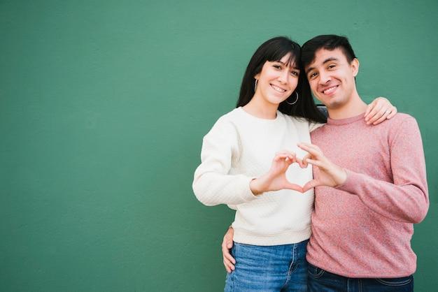 Sonriente pareja doblando las manos en forma de corazón