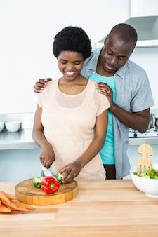 Sonriente pareja embarazada cortar verduras en la cocina en casa