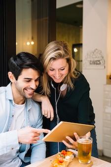 Sonriente pareja en café mirando tableta
