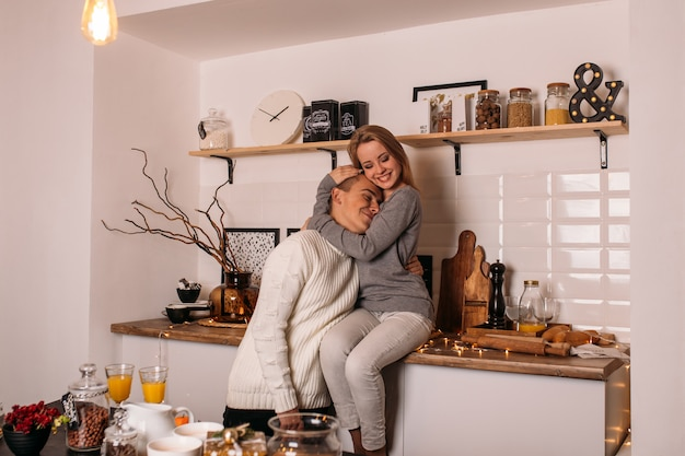 Sonriente pareja de enamorados en la cocina en casa