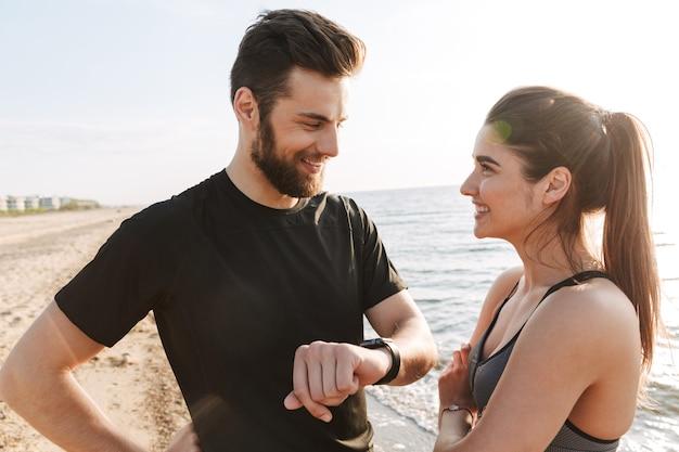 Sonriente pareja joven deporte mostrando