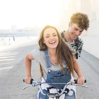 Sonriente pareja joven en bicicleta