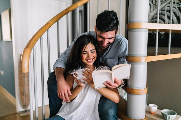 Sonriente, pareja joven, sentado, en, escalera, lectura, libro