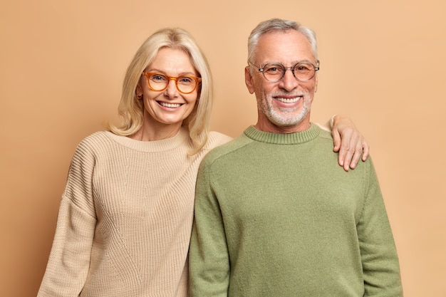 Sonriente pareja madura abrazar mira con alegría la pose de la cámara para el retrato de familia.los niños felices vinieron a visitarlos. usan lentes transparentes, puentes casuales aislados sobre una pared marrón.