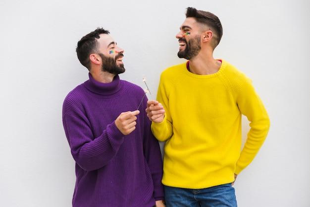 Sonriente pareja masculina con luces de bengala