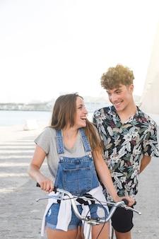Sonriente pareja mirándose mientras conduce bicicleta