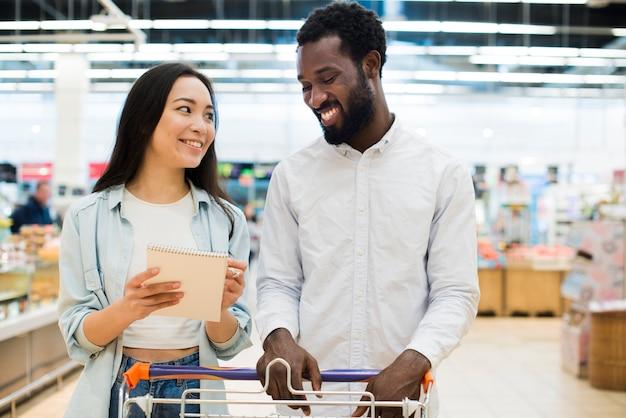Sonriente pareja multiétnica comprando productos en supermercado