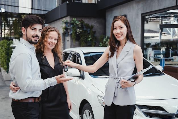 Sonriente pareja obtener la clave de un coche nuevo.