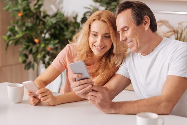 Sonriente pareja optimista divertida disfrutando el fin de semana en casa y divirtiéndose mientras usa dispositivos digitales y comparte alegría