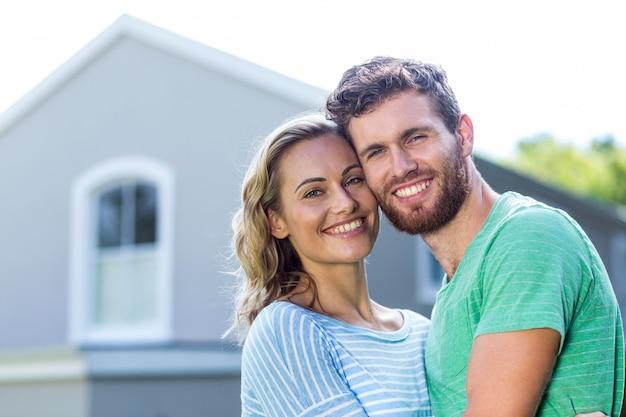 Sonriente pareja de pie contra la casa