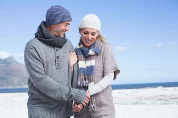 Sonriente pareja de pie en la playa en ropa de abrigo