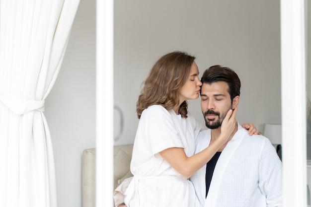 Sonriente pareja relajante y parejas abrazándose y besando la frente en la cama