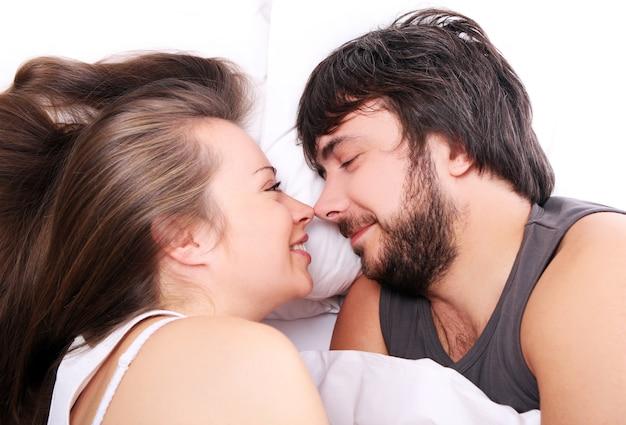 Sonriente pareja relajarse en la cama