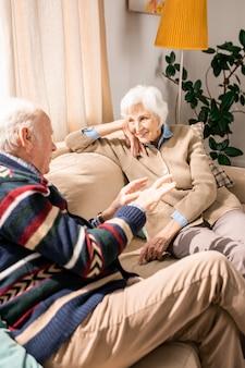 Sonriente pareja senior chateando en casa