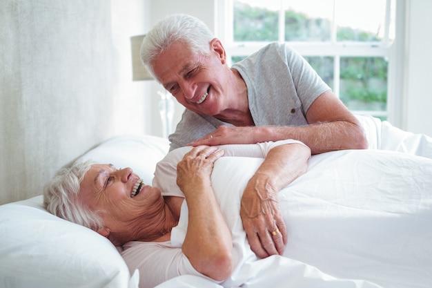 Sonriente pareja senior descansando en la cama