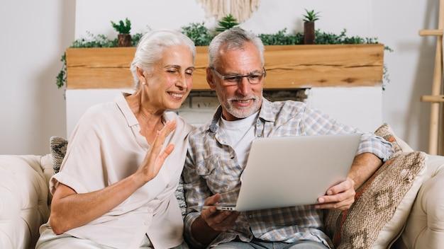 Sonriente pareja senior haciendo video chateando en la computadora portátil