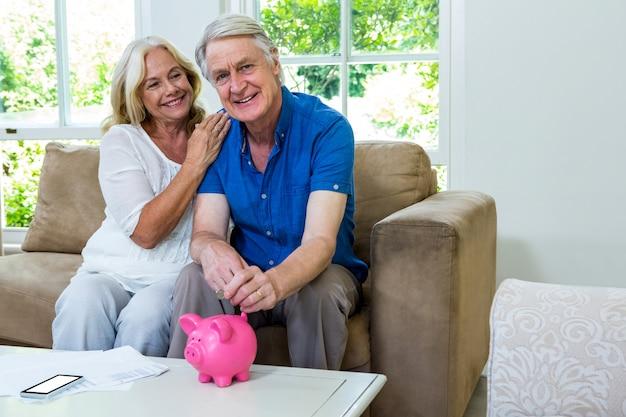 Sonriente pareja senior poniendo monedas en hucha en casa