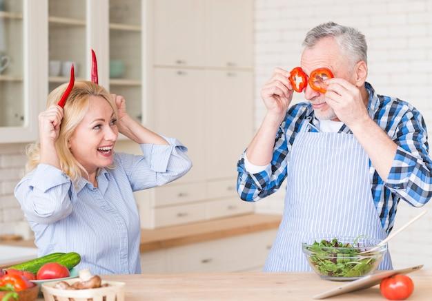 Sonriente pareja senior riéndose con chiles rojos y pimientos parados en la cocina