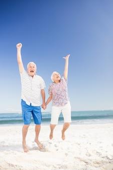 Sonriente pareja senior saltando