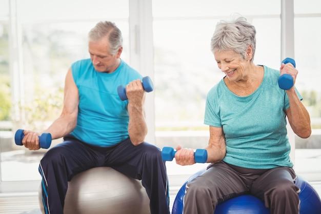 Sonriente pareja senior sosteniendo pesas mientras hace ejercicio