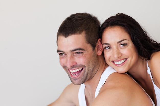 Sonriente pareja sentada en la cama