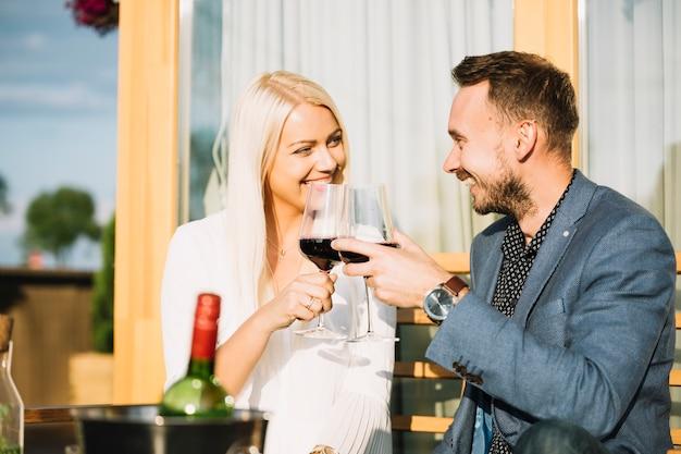 Sonriente pareja sentada en el restaurante brindando vino tinto