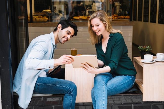 Sonriente pareja sentada en la cafetería con tableta