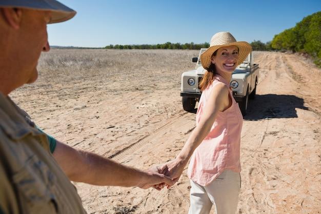 Sonriente pareja tomados de la mano en el paisaje