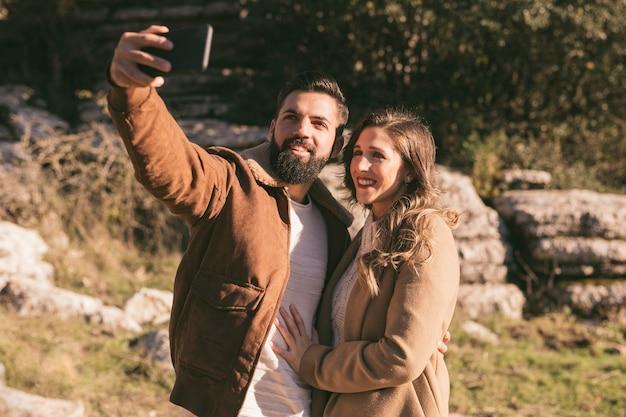 Sonriente pareja tomando un selfie en la naturaleza