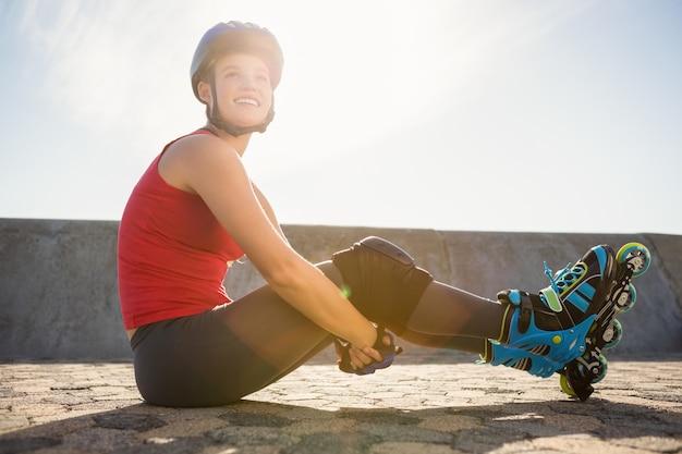 Sonriente patinador rubio deportivo sentado en el suelo