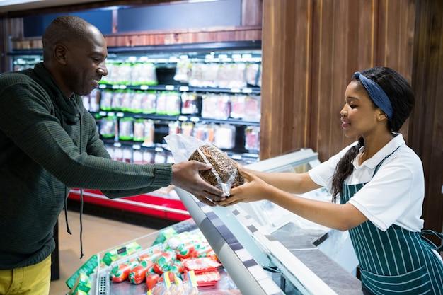 Sonriente personal femenino dando una mercancía al cliente