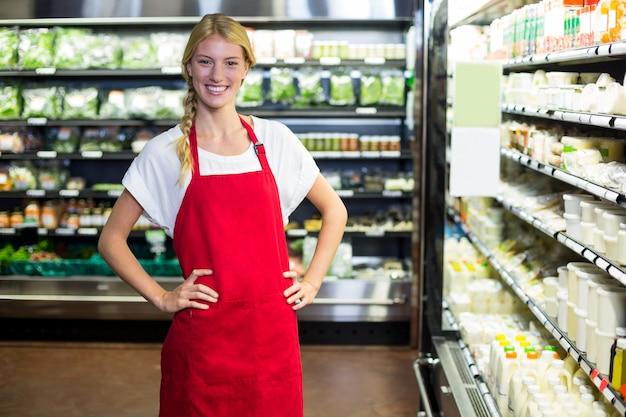 Sonriente personal femenino de pie con la mano en la cadera en la sección de comestibles