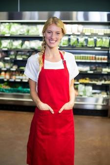 Sonriente personal femenino de pie con las manos en el bolsillo en la sección de comestibles