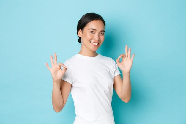 Sonriente, segura de sí misma, una chica asiática bonita asegura todo bajo control, garantiza la calidad, garantiza un servicio perfecto, muestra gestos correctos y asiente con la cabeza en señal de aprobación, de pie frente a la pared azul satisfecha