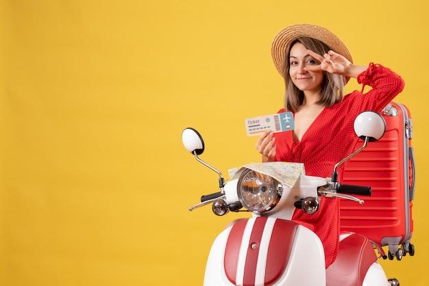 Sonriente señorita en vestido rojo sosteniendo boleto de avión en ciclomotor