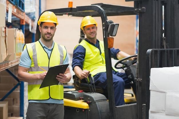 Sonriente trabajador de almacén y conductor de montacargas