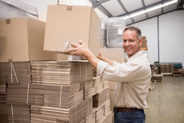 Sonriente trabajador de almacén tomando una caja en un gran almacén