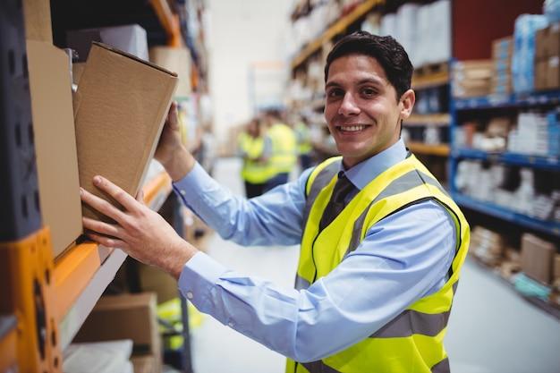 Sonriente trabajador de almacén tomando paquete en el estante en almacén