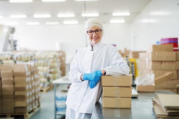 Sonriente trabajadora apoyándose en cajas. almacén interior.