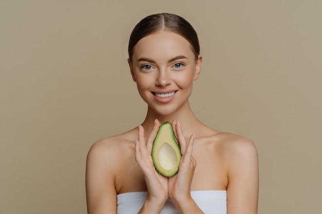 Sonriente y tranquila mujer europea con cabello peinado sostiene el aguacate como recomendación para una mascarilla nutritiva