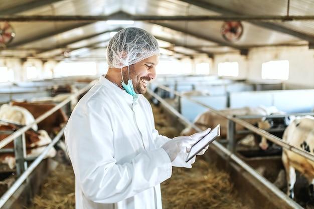 Sonriente veterinario caucásico sin afeitar en uniforme, con guantes y redecilla con tableta mientras está de pie en el establo.
