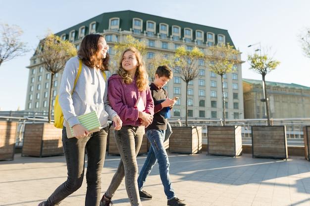 Sonrientes adolescentes estudiantes hablando y avanzando
