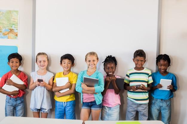 Sonrientes alumnos de pie con tecnología