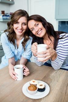 Sonrientes amigas sosteniendo tazas de café en la mesa
