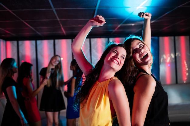 Sonrientes amigos bailando en la pista de baile