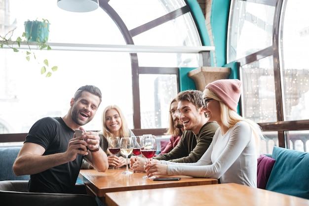 Sonrientes amigos en la cafetería bebiendo alcohol y hacer una selfie.