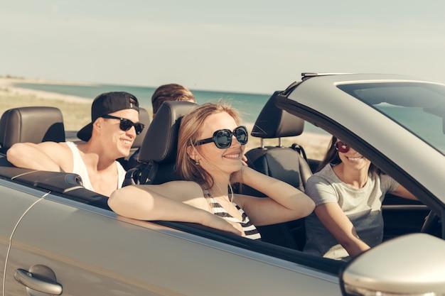 Sonrientes amigos conduciendo un automóvil cerca del mar y divirtiéndose