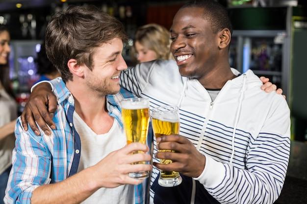 Sonrientes amigos degustando cerveza con sus amigos